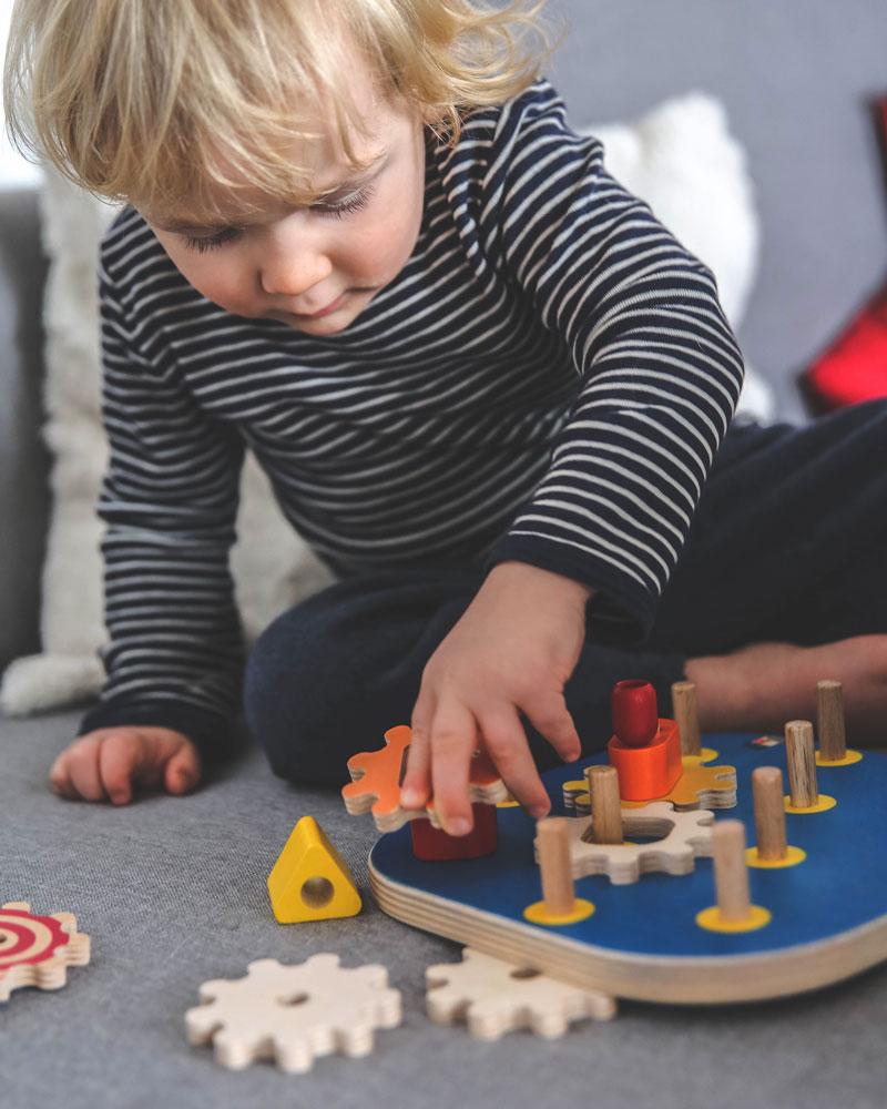 Kind met motoriekbord houten speelgoed van Selecta