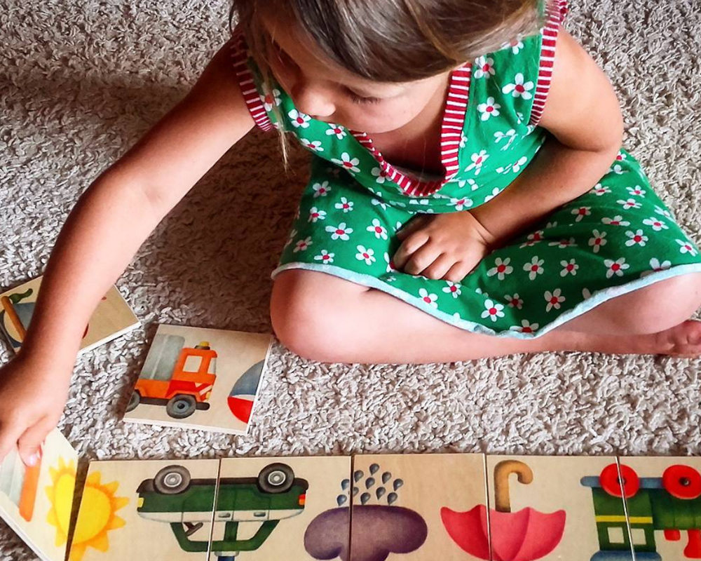 Kind met plaatjesstraat houten speelgoed van Selecta